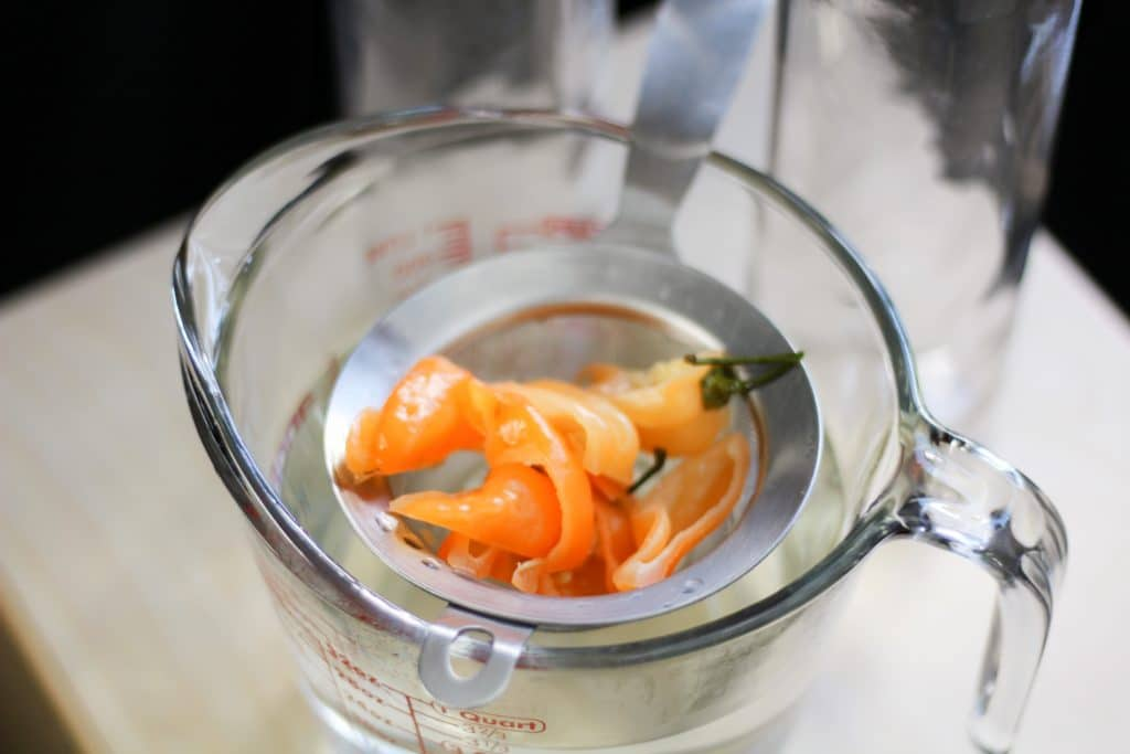 sous vide infused vodka peppers in strainer
