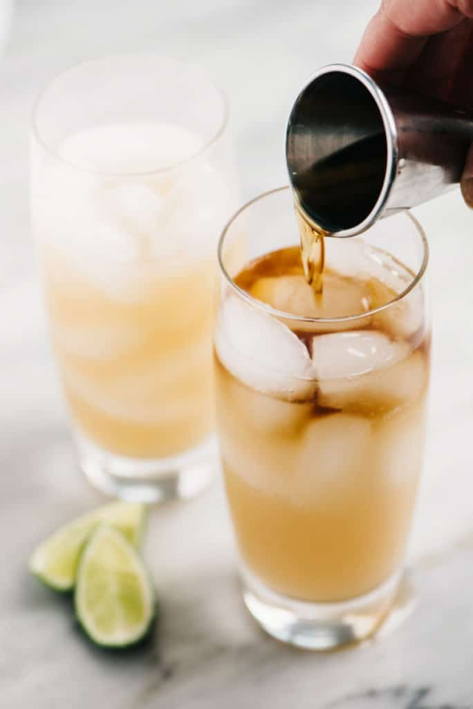 Dark and stormy drink vertical rum pouring small