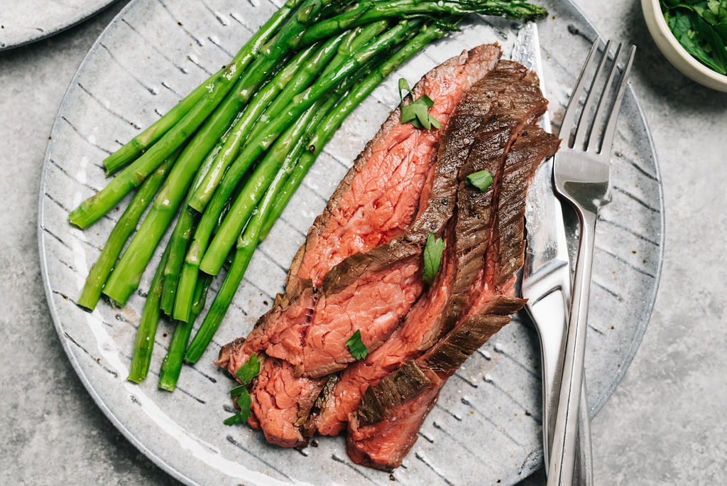 Flank steak on plate with asparagus