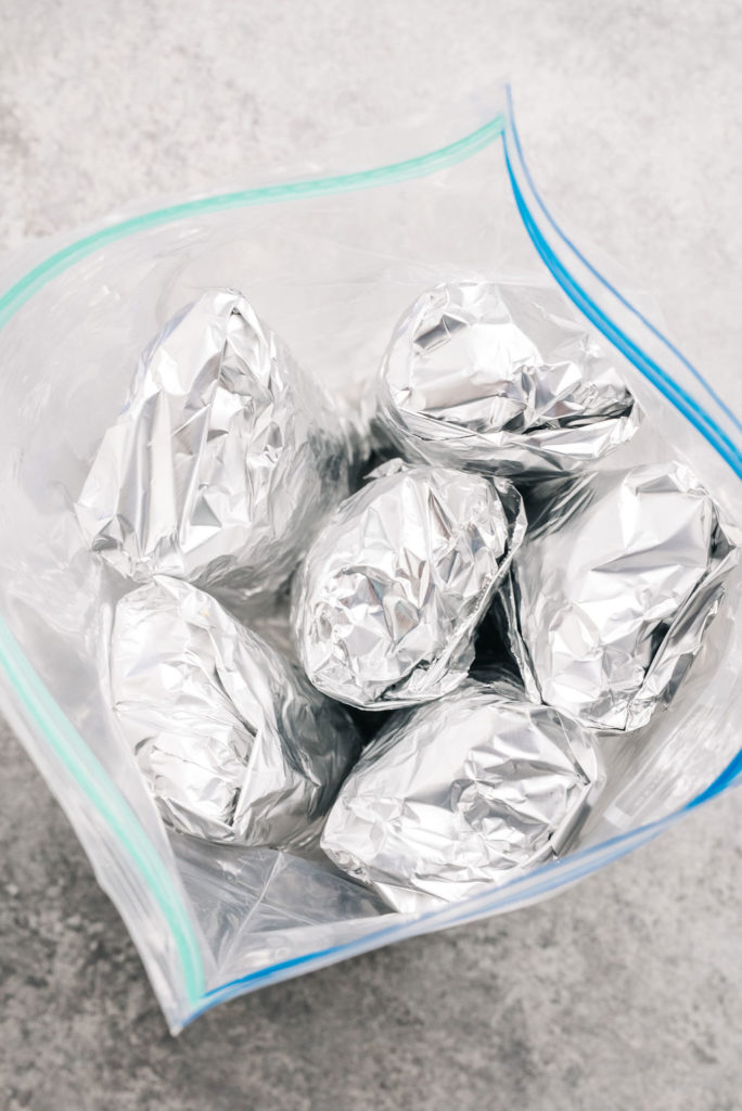 Freezer friendly breakfast burritos in foil vertical
