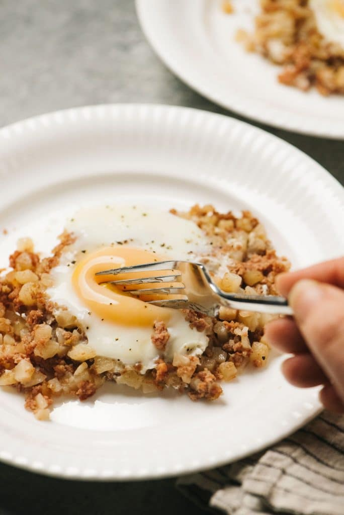 Cutting into egg corned beef hash on plate verticle