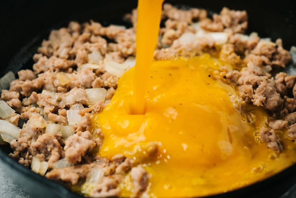 Eggs pouring in sausage and onion