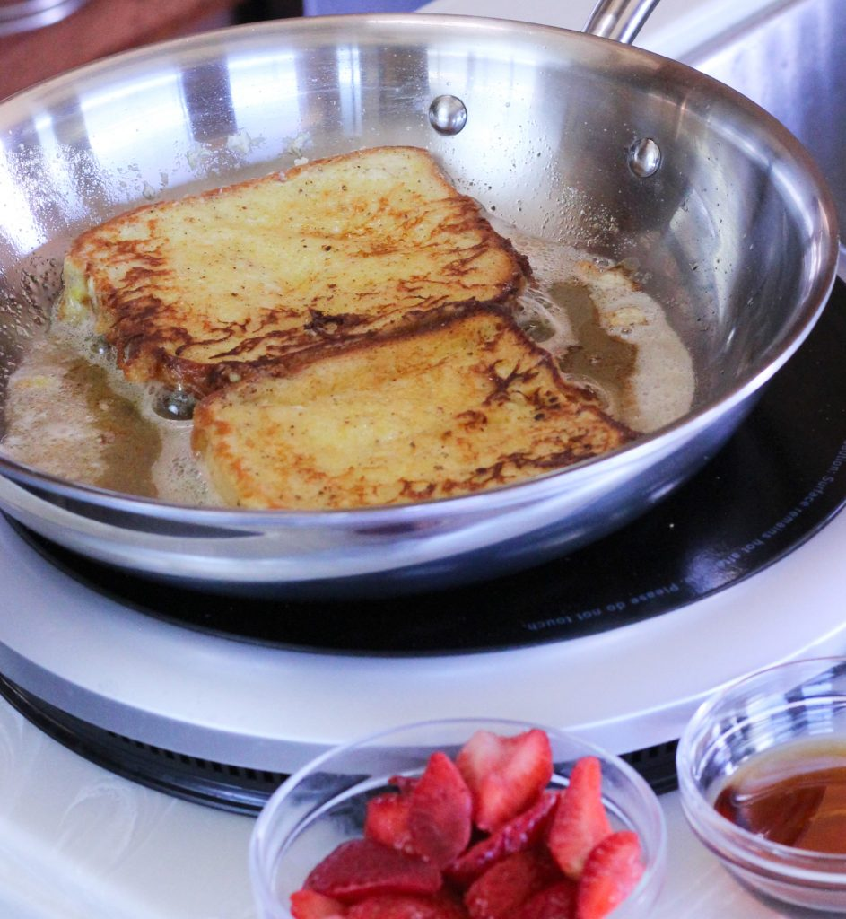 french toast cooking in pan with syrup and strawberries
